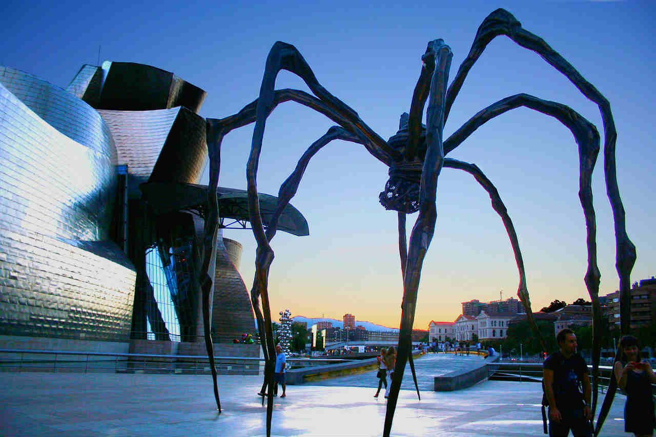 People walking under Louise Bourgeoius spider art